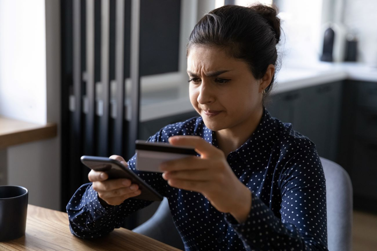 A woman looks at her phone and credit card as she deals with credit card fraud