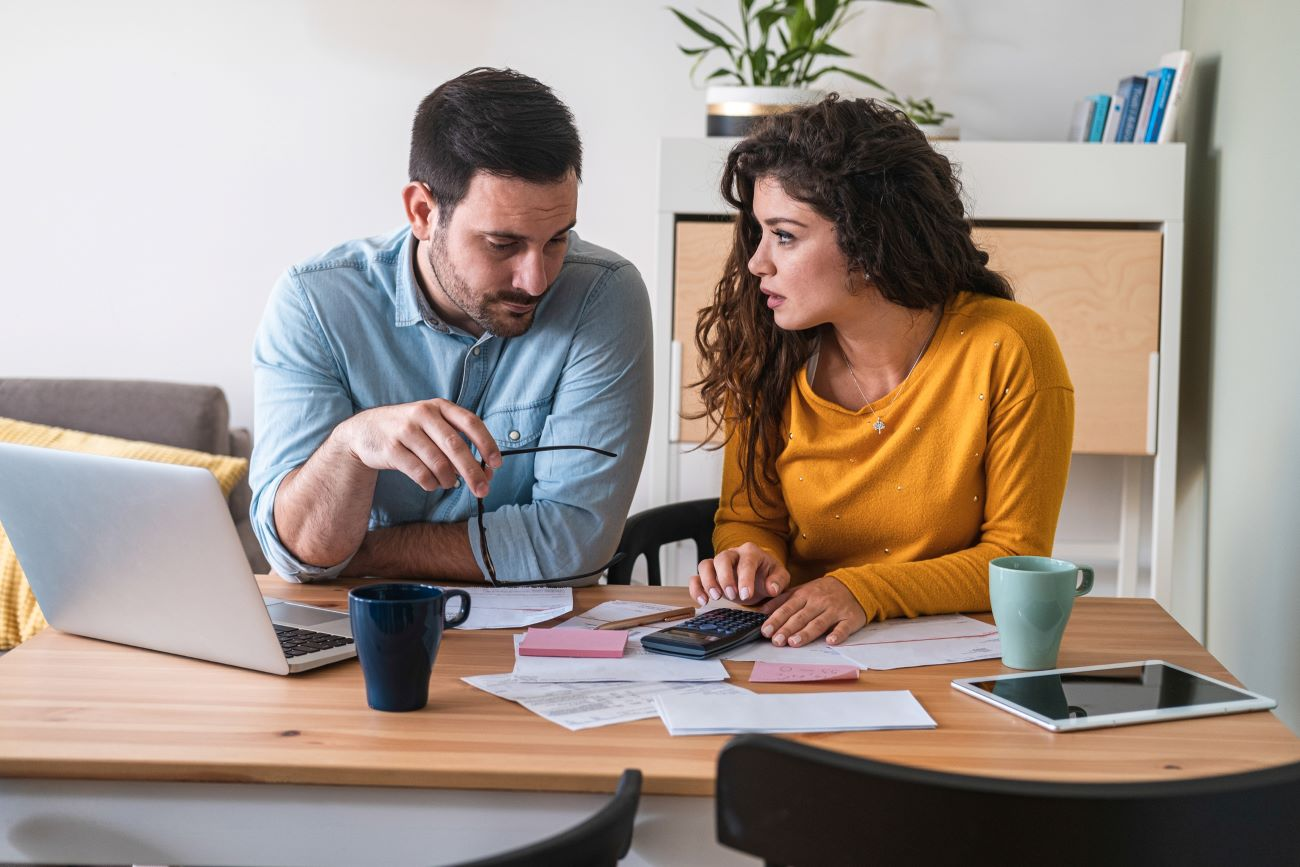 a couple looks at their finances to decide