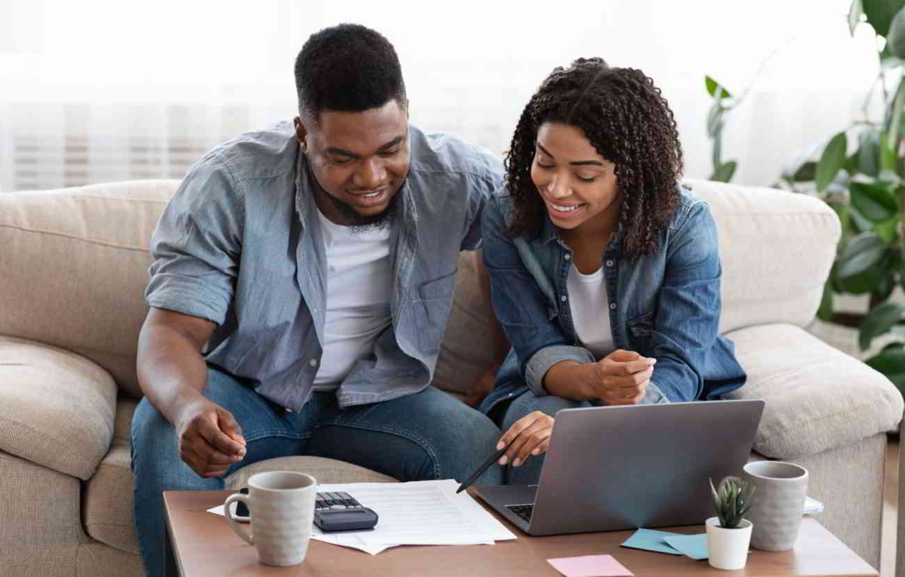 A young couple looks at their finances and discusses a family budget