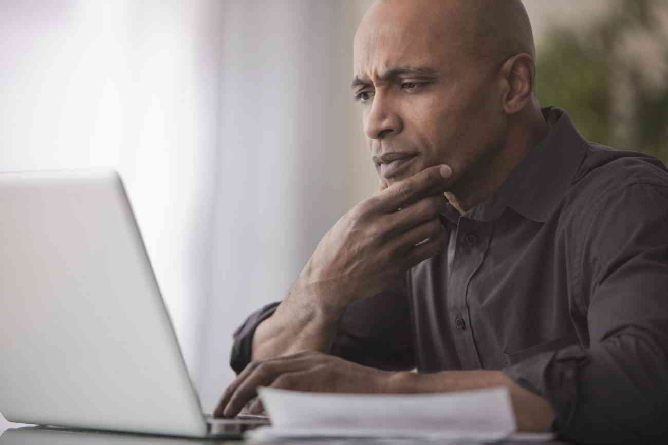 A man uses his laptop computer to research personal loans