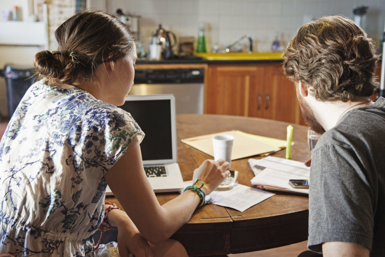 Young couple working together at home on personal loan application