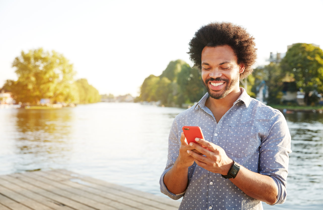 A man uses a smartphone app to make a loan payment