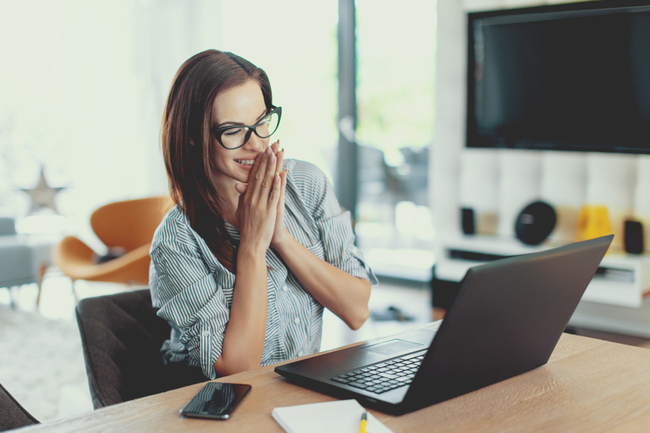 A woman looks at her computer with a happy expression because she is approved for a personal loan