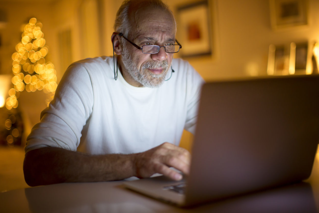 A man uses his computer to research his credit score