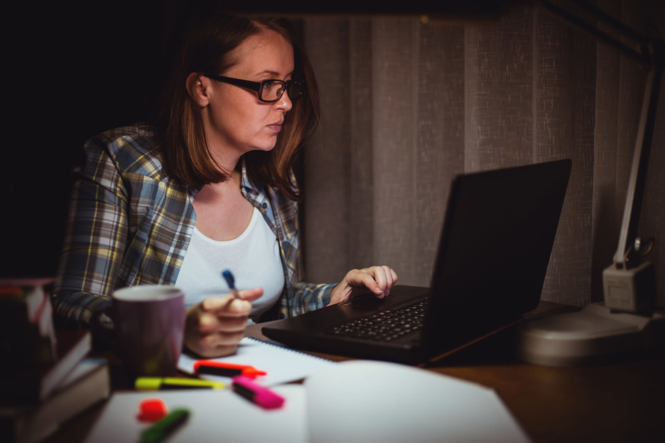 A woman searches for a personal loan on her computer late at night.